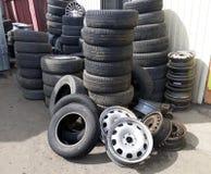 堆老轮胎和轮子外缘在车间附近 免版税库存照片