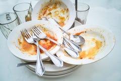 堆肮脏的油腻的板材,玻璃,在膳食以后的叉子匙子 图库摄影