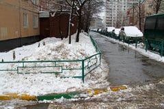 堆肮脏的雪在一个房子的围场在Vidnoe 库存图片