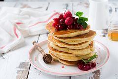 堆自创小的薄煎饼用蜂蜜、新鲜的莓和红浆果在老轻的木背景 免版税图库摄影