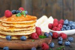 堆自创薄煎饼用新鲜的蓝莓、莓和枫蜜 免版税库存图片