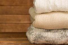 堆舒适被编织的温暖的毛线衣,木背景 库存图片