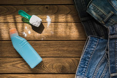 堆蓝色牛仔裤穿衣与洗涤剂和洗衣粉  免版税图库摄影