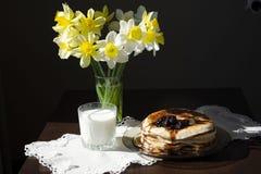 堆薄煎饼用在板材的黑醋栗果酱在黑桌,可口点心上早餐 库存图片