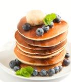堆薄煎饼用新鲜的蓝莓、槭树黄油和糖浆 免版税图库摄影