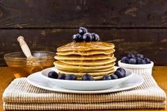 堆薄煎饼用新鲜的蓝莓和蜂蜜 免版税库存图片
