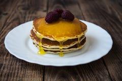 堆薄煎饼用蜂蜜和莓在白色板材 免版税库存图片