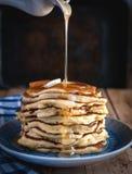 堆薄煎饼用黄油和下毛毛雨的蜂蜜在木背景 免版税库存图片