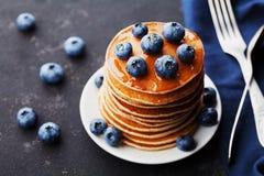 堆被烘烤的美国薄煎饼或油炸馅饼用蓝莓和蜂蜜糖浆在土气黑背景 可口点心 免版税图库摄影