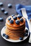 堆被烘烤的美国薄煎饼或油炸馅饼用蓝莓和蜂蜜糖浆在葡萄酒染黑桌 可口点心 免版税图库摄影