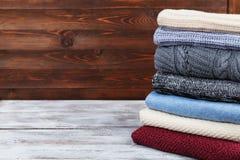 堆被编织的冬天衣裳和羊毛毛线衣在木背景 复制文本的空间 库存照片