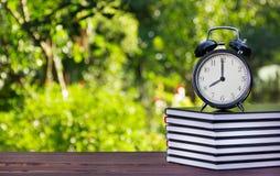 堆课本和一个时钟在一张木桌上 堆书和一个闹钟在绿色弄脏了背景 培训 免版税库存照片