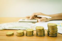 堆金黄硬币和美元钞票 库存照片