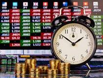 堆金黄硬币,在右边的时钟 库存图片