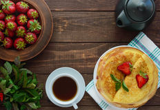 堆金黄薄煎饼用草莓和草莓酱,薄菏装饰小树枝  库存照片