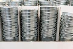 堆银色锡在白色波纹状的箱子用桶提 免版税库存图片