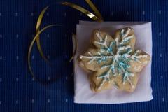 堆顶上的看法雪花塑造了在白色餐巾的糖屑曲奇饼有蓝色背景 库存照片