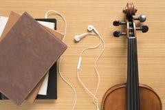 堆顶视图有耳机和小提琴的笔记本 免版税库存图片