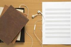 堆顶视图有耳机的笔记本和音乐给pape雇用职员 库存图片