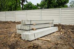 堆预制混凝土在新鲜的底层上的墙板,修筑在建造场所的墙壁外面 库存照片