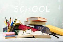 堆颜色书、镜片、文具和放大镜在桌上和文本& x22; School& x22;在绿色背景 图库摄影