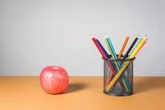 堆颜色铅笔和苹果 库存图片