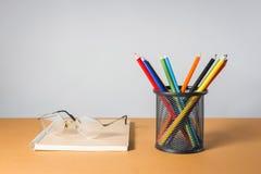 堆颜色铅笔和玻璃在笔记本 库存图片