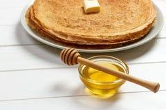 堆鲜美薄煎饼用黄油和蜂蜜早餐 免版税库存照片