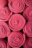 堆滚动充满活力的桃红色上色了羊毛毯子,背景的垂直的照片 免版税库存照片