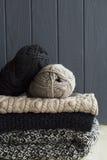 堆从被编织的针织品的温暖的衣裳在灰色木bac 免版税库存图片
