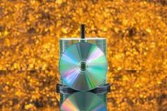 堆50 CD/DVD在defocused橙色的背景中 图库摄影