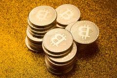 堆bitcoin在金黄闪烁的背景铸造 免版税库存照片