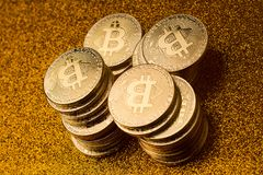 堆bitcoin在金黄闪烁的背景铸造 免版税库存图片