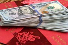堆USD在朱红色的小包背景的100美元 免版税库存图片