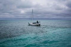 堡礁,伯利兹- 2013Sailboat 12月1日,开汽车远离清楚的绿松石水的伯利兹船坞 库存图片