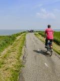 堤堰的骑自行车者 免版税库存图片