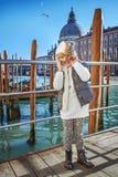 堤防的孩子在威尼斯,意大利佩带的威尼斯式面具 免版税库存照片