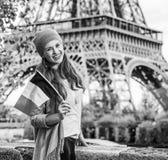 堤防的端庄的妇女在显示旗子的埃佛尔铁塔附近 库存照片