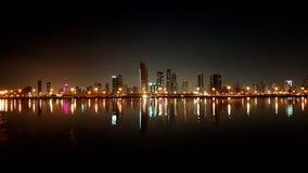 堤防 夜城市的视图沿海岸区有摩天大楼的和 免版税库存照片