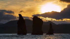 堪察加半岛海景:在Avacha海湾太平洋的三个兄弟岩石在日落 股票录像