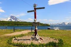 堪察加半岛,俄罗斯- 2018年7月7日:在库页湖附近的方向标岗位以火山伊利因斯基火山为背景 库存图片