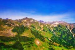 堪察加 松鸡爱本质歌曲通配木头 绿色领域和火山 从直升机的视图 免版税图库摄影