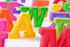 塑料五颜六色的字母表信件在白色关闭  免版税库存照片