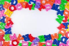 塑料五颜六色的字母表信件框架在白色的 免版税图库摄影