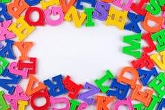 塑料五颜六色的字母表信件框架在白色的 免版税库存图片