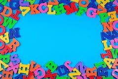 塑料五颜六色的字母表信件框架在蓝色的 免版税库存照片