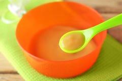 塑料匙子和碗用婴儿食品 免版税库存图片