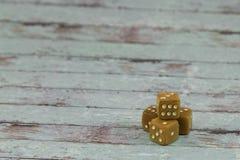 塑料在白色木表上切成小方块:赌博的题材 库存照片