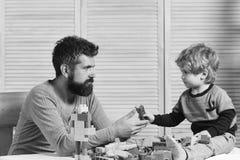 塑料块爸爸和孩子修造  父亲和儿子有严肃的面孔的使用与玩具砖 免版税库存照片