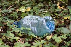 塑料垃圾在森林卷起了自然 塑胶容器ly 免版税库存图片